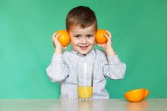 Rapaz pequeno com laranjas e suco imagem de stock royalty free
