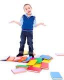Rapaz pequeno com livros caídos Imagem de Stock Royalty Free