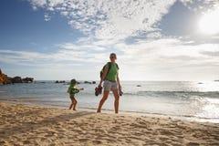 Rapaz pequeno com mãe em uma caminhada da família pelo mar tropical imagem de stock royalty free