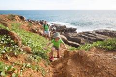 Rapaz pequeno com mãe em uma caminhada da família pelo mar tropical fotos de stock royalty free