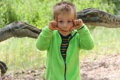 Rapaz pequeno com mãos por seus olhos com os dinossauros dentro atrás imagens de stock royalty free