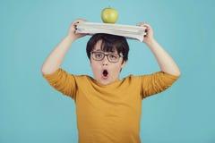 Rapaz pequeno com maçã e os livros verdes imagens de stock royalty free