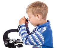 Rapaz pequeno com microscópio fotos de stock