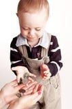 Rapaz pequeno com moedas Imagens de Stock