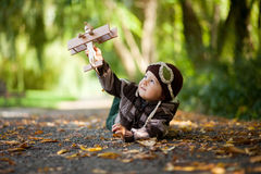 Rapaz pequeno com o chapéu do aviador, encontrando-se na terra em um parque Foto de Stock Royalty Free