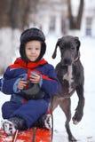 Rapaz pequeno com o cão preto grande Imagem de Stock