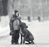 Rapaz pequeno com o cão preto grande Imagem de Stock Royalty Free