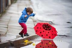 Rapaz pequeno com o guarda-chuva, saltando nas poças imagens de stock royalty free