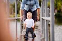 Rapaz pequeno com o pai que faz primeiras etapas na natureza Fotografia de Stock