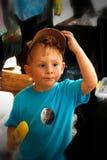 Rapaz pequeno com o tampão em comer um picolé amarelo Fotos de Stock Royalty Free