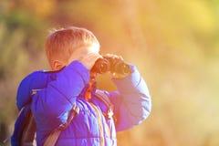 Rapaz pequeno com os binóculos que caminham nas montanhas Imagens de Stock Royalty Free
