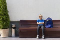 Rapaz pequeno com os vidros que sentam-se no banco e na espera outdoors imagem de stock
