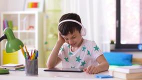 Rapaz pequeno com PC e fones de ouvido da tabuleta em casa video estoque