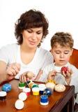 Rapaz pequeno com sua pintura da mãe os ovos da páscoa Imagem de Stock Royalty Free