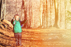 Rapaz pequeno com a trouxa que trekking na floresta do outono Imagem de Stock