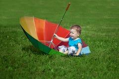 Rapaz pequeno com um guarda-chuva grande do arco-íris imagens de stock royalty free