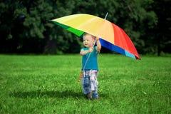 Rapaz pequeno com um guarda-chuva grande do arco-íris foto de stock
