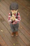 Rapaz pequeno com uma cara séria que aponta uma arma de madeira do brinquedo na câmera imagem de stock