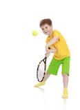 Rapaz pequeno com uma raquete de tênis ao bater foto de stock royalty free