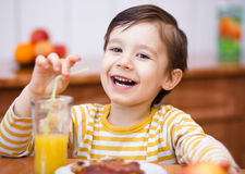Rapaz pequeno com vidro do sumo de laranja Fotos de Stock