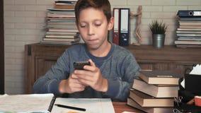 Rapaz pequeno confundido pelo smartphone de fazer trabalhos de casa video estoque