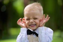 Rapaz pequeno considerável em um terno para rir exterior fotografia de stock