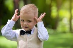 Rapaz pequeno considerável em um terno para rir exterior fotografia de stock royalty free