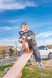 Rapaz pequeno contente do  de Ð em um teetertotter Imagem de Stock Royalty Free