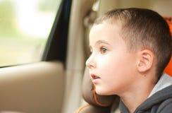 Rapaz pequeno curioso no carro que olha a janela Foto de Stock