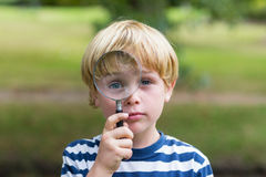 Rapaz pequeno curioso que olha através da lupa Imagem de Stock