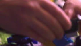 Rapaz pequeno da criança da criança com assento do cabelo do blondi cercado brinquedos e por jogo com lego e câmera dos blocos de vídeos de arquivo