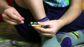 Rapaz pequeno da criança da criança com assento do cabelo do blondi cercado brinquedos e por jogo com lego dos blocos de apartame video estoque