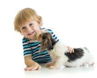 Rapaz pequeno da criança com seu cão de cachorrinho Isolado no fundo branco fotos de stock