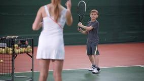 Rapaz pequeno de ensino do instrutor fêmea que joga o tênis Mulher no equipamento branco do esporte que está no amarelo de jogo d video estoque