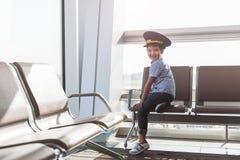 Rapaz pequeno de sorriso alegre no terminal fotografia de stock royalty free
