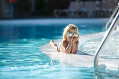 Rapaz pequeno de sorriso bonito com os óculos de sol que encontram-se na piscina Fotografia de Stock