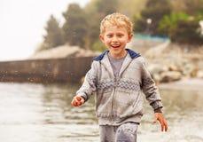 Rapaz pequeno de sorriso bonito corrido em gotas da água imagem de stock