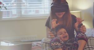 Rapaz pequeno de sorriso bonito que joga com sua irmã mais velha na cama, quando ela que usa um VR para jogar um jogo, irmão amig vídeos de arquivo