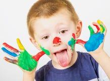 Rapaz pequeno de sorriso com as mãos pintadas em pinturas coloridas Imagens de Stock Royalty Free