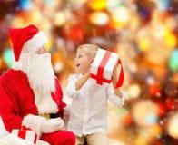 Rapaz pequeno de sorriso com Papai Noel e presentes Imagem de Stock