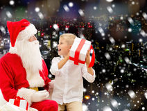 Rapaz pequeno de sorriso com Papai Noel e presentes Imagens de Stock