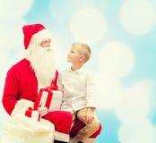 Rapaz pequeno de sorriso com Papai Noel e presentes Foto de Stock