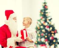 Rapaz pequeno de sorriso com Papai Noel e presentes Fotografia de Stock Royalty Free