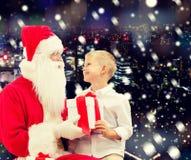 Rapaz pequeno de sorriso com Papai Noel e presentes Fotos de Stock Royalty Free