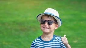 Rapaz pequeno de sorriso feliz do retrato nos óculos de sol e no chapéu que têm a dança do divertimento no parque do verão video estoque