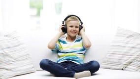 Rapaz pequeno de sorriso nos fones de ouvido em casa video estoque