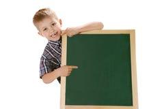 Rapaz pequeno de sorriso que aponta um sinal no quadro-negro da escola Foto de Stock