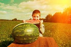Rapaz pequeno de sorriso que come a melancia Fotografia de Stock Royalty Free