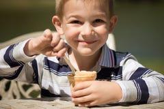Rapaz pequeno de sorriso que come o gelado Fotos de Stock