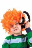Rapaz pequeno de sorriso que escuta a música no headphon Imagem de Stock Royalty Free